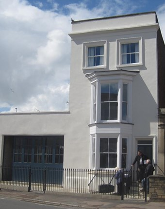 A 3 story townhouse with white stucco exteriof and new railings