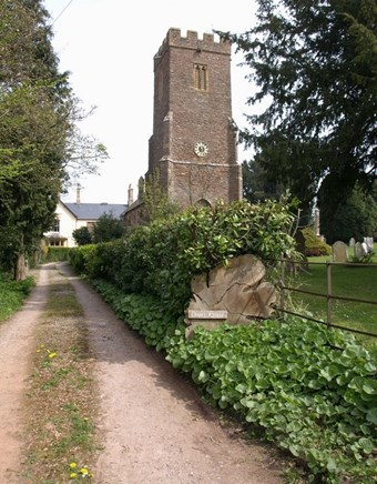 A medieval church with a square tower stands at the end of a sandy lane.