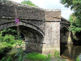A view from the river bank of an old stone bridge, with wide four-centred arches.