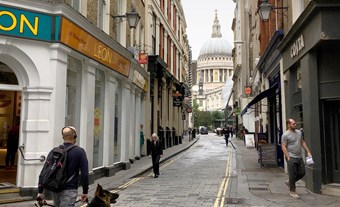 View west down narrow London street towards St Paul's Cathedral dome.