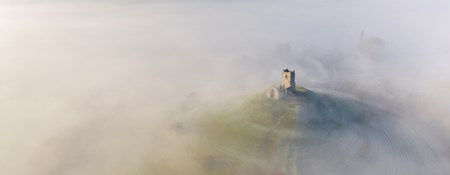 Aerial photograph of St Michael's Church, Burrow Mump in Somerset mist covering surrounding area