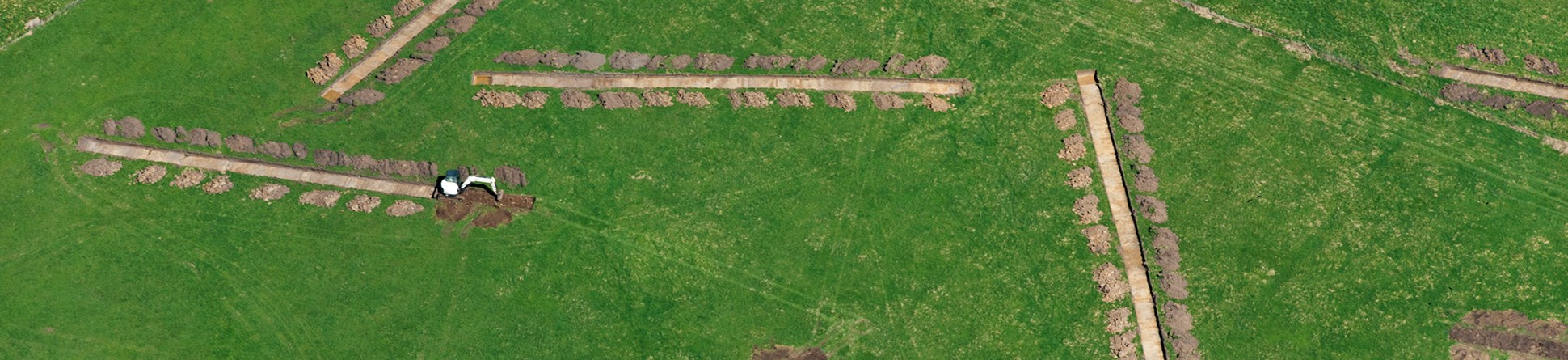 An aerial photograph of eight trial archaeological trenches in a green field.