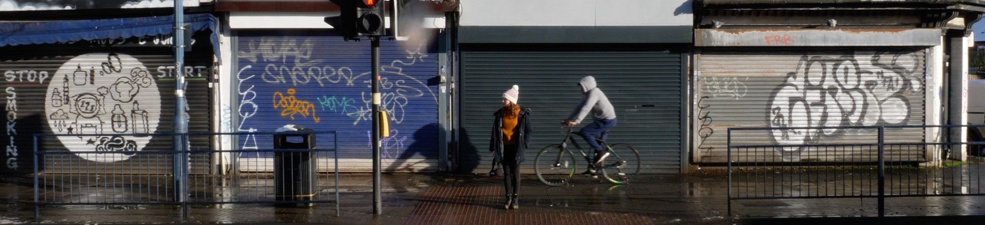Woman stands waiting at a pelican crossing as a cyclist passes behind her on the pavement. Behind her along the street, shops are closed and most of the shop front security shutters have graffiti.