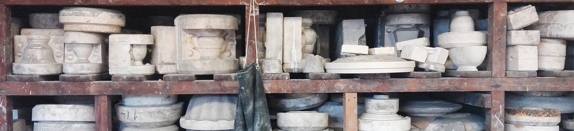 Photograph of shelves in a workshop stacked with plaster moulds for casting tableware ceramics. Varying sizes of moulds for teapots, bowls and cups are on display.