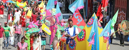 A carnival parade makes its way up a road. People wear colourful clothing, and carry flags. At the head of the procession a man walks inside a boat made of fabric stretched around a frame.