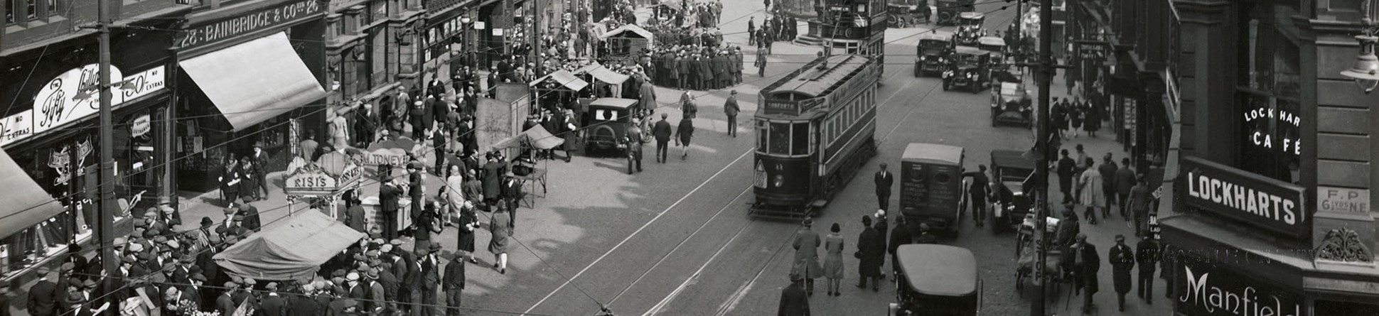 Black and white photo of a busy street scene 1925-1930.