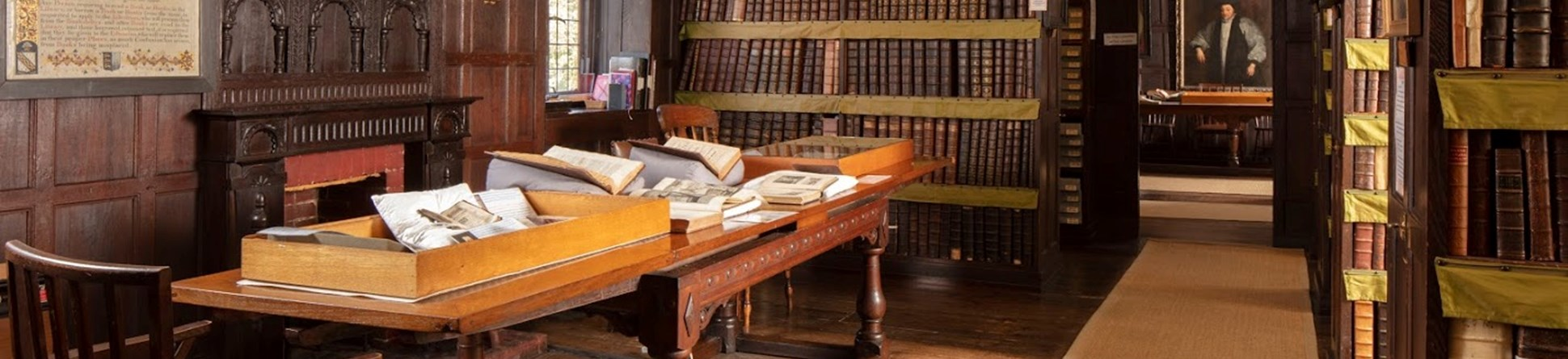 The library room shows dark wood panelling, wooden floorboard and dark wood bookcases with a long table to the left, covered in historic books. Historic portraits line the walls.