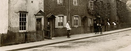 Sepia toned photo of people standing outside a row of houses.