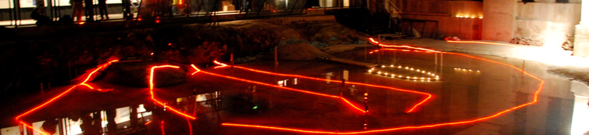 Red lighting shows the outline of archaeological remains of a building preserved beneath a modern development.