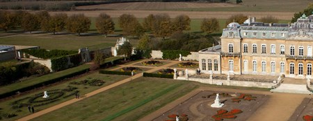 Low level, colour aerial photograph showing a grand country house and gardens with formal planting and statues