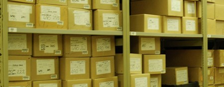 Labelled archive boxes on shelves within an archives store
