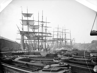 In the A black and white Victorian photo of London docks. Small boats are crowded together in the foreground. There are old, masted sailing ships in the background.