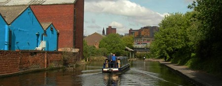 View along a canal in Birmingham, with canal boat and industrial buildings.