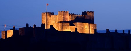 A large medieval castle keep dramatically floodlit at twilight.
