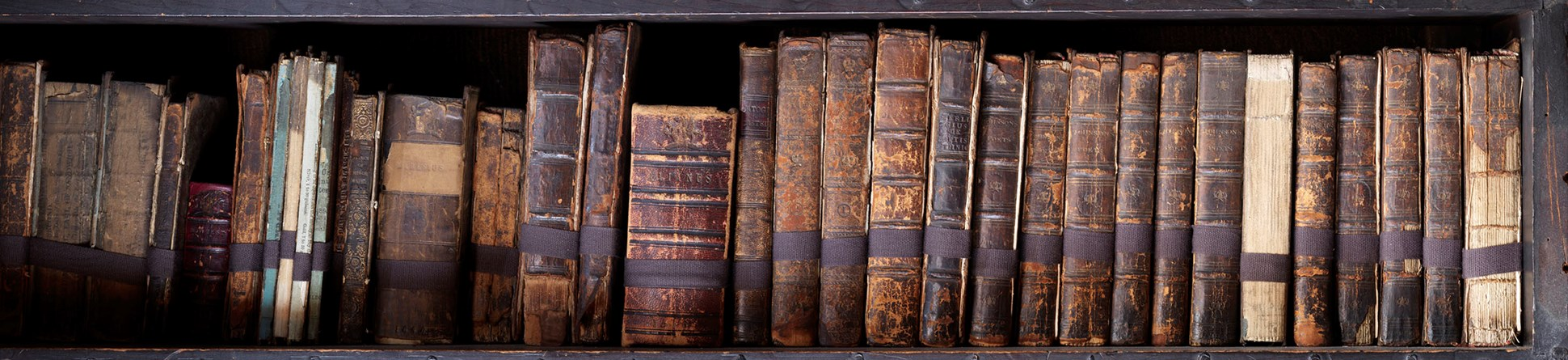 Old leather-bound books on three shelves of Chetham's Library, Long Millgate, Manchester.