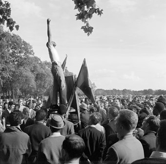 General view of a crowd at speakers corner in Hyde Park, with a young black man on the platform with arm outstretched to the sky.  'london observed' negatives hyde park speakers corner greater london city of westminster paddington bayswater and knightsbridge