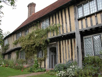 Timber framed house with leaded windows and borders of garden and climbing plants.