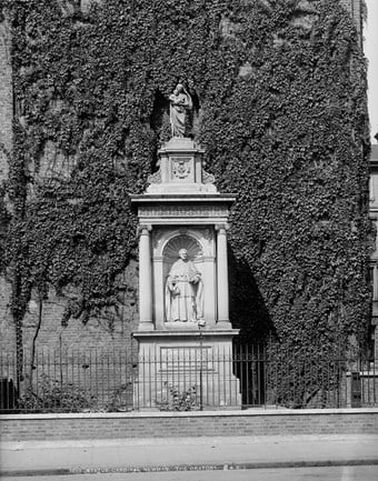 Black and white photo of a white monument next to a building wall covered in ivy