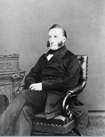 Black and white portrait of a man sitting in a leather chair