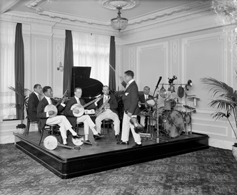Band playing drums, saxaphone and banjos sitting on a platform with the conductor holding a violin and using the bow as a baton