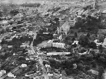 A view of St Albans Cathedral in 1920. In the foreground is a long narrow building - one of the towns'