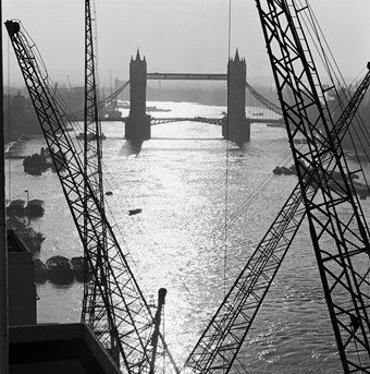 Archive photograph of Tower Bridge in the mist viewed from riverside gantries, looking east along the River Thames
