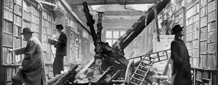 Archive photograph showing three men calmly browsing books on surviving library shelves amid the rubble of a roofless shell