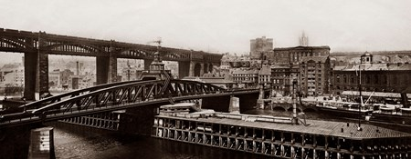 Archive sepia image showing a river with two bridges and a city beyond.