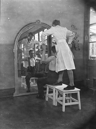A physiotherapist directing remedial exercises, whilst standing on a stool behind a patient seated in front of a mirror