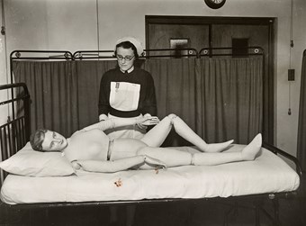 Nurse with the special jointed model which student nurses in the training school use for practical work
