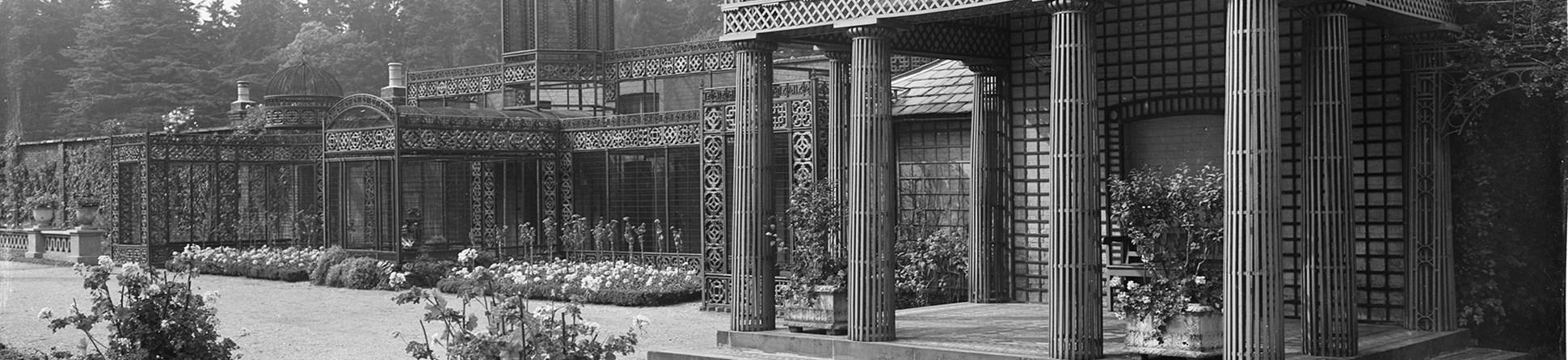 archive black and white photograph of a classical style colonnaded garden building and an elaborate wrought-iron aviary