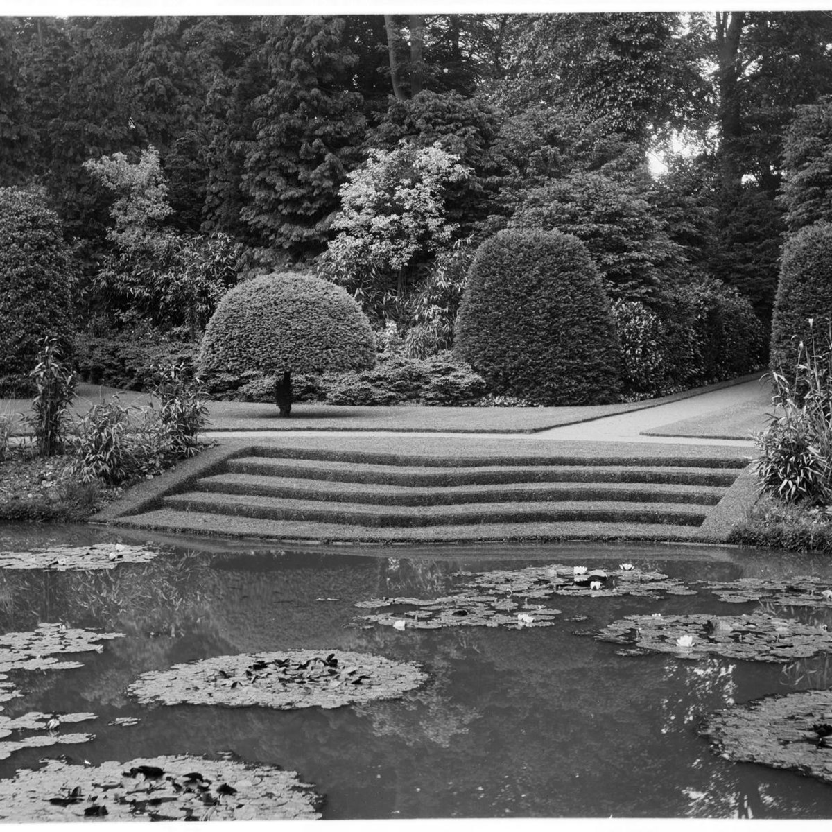 Archive black and white photograph of steps leading down to a pond with several groups of