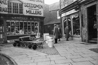 archive black and white photograph of shoppers, wheelbarrows and dustbins displayed on the pavement in front of shops