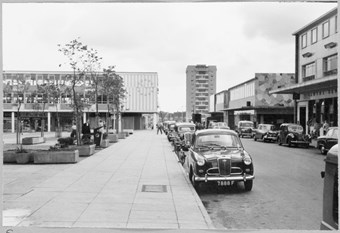 archive black and white photograph of a street scene with people and vehicles