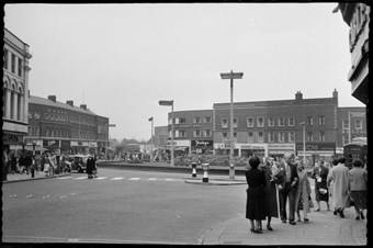 archive black and white photograph of a busy street scene with people on the pavements