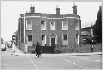 archive black and white photograph of a double-bayed house on a street corner with a pedestrian crossing the road in the foreground