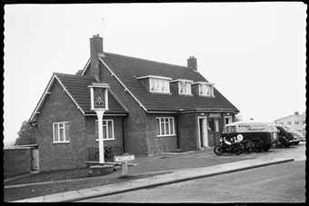 archive black and white photograph of a building with vehicles parked and a sign