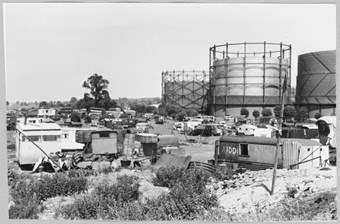 archive black and white photograph of three gasholders with caravans in the foreground