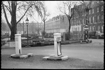 archive black and white photograph of street furniture including traffic bollards, no-entry sign and a streetlamp.