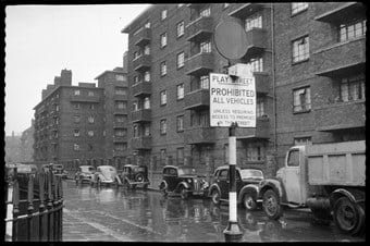archive black and white photograph of a street scene with parked vehicles