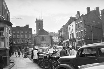 archive black and white photograph of  a busy street scene with people and vehicles