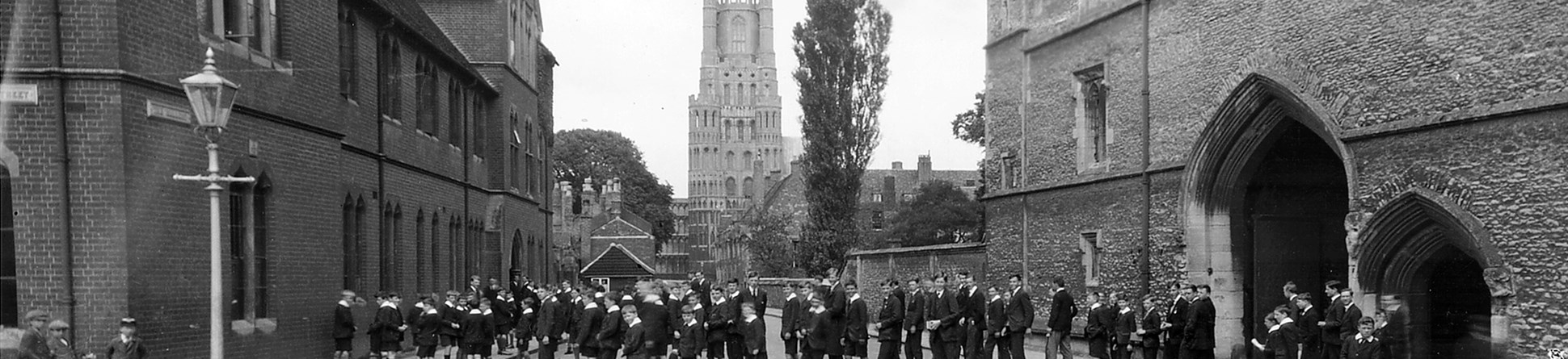 Archive black and white photograph of a group of schoolboys in the street between a brick building and a flint and stone medieval gatehouse, with a church tower in the background.