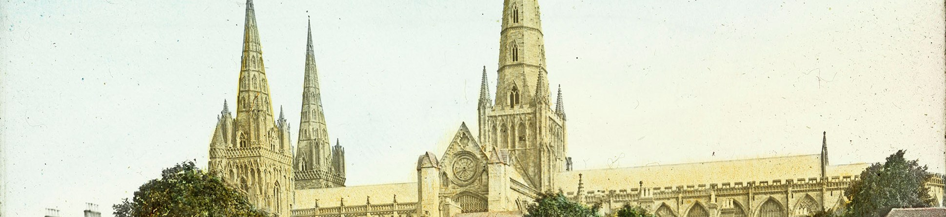 Arcive coloured photo of a Cathedral with a spire behind trees.