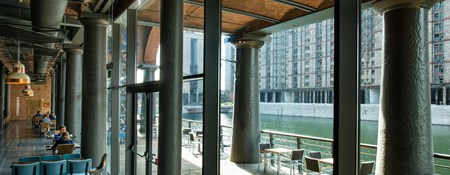 View of a cafe interior and across the dock to other buildings.