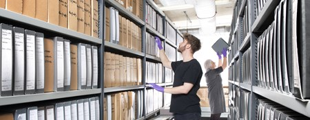 Two volunteers browse and select boxes of photos off the Historic England Archive shelves