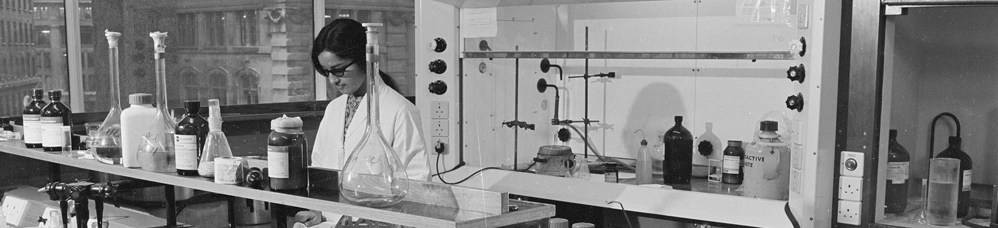 Black-and-white photograph of a female scientist at work in a laboratory at King's College London