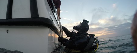 A diver wearing SCUBA equipment prepares to climb up a ladder from a boat following a dive.