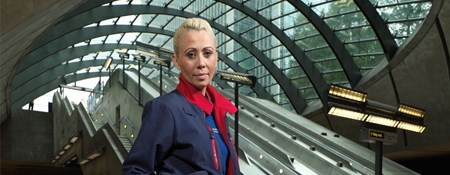 Female London Underground employee standing at the bottom of escalators at Canary Wharf station.