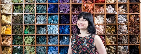 Young woman photographed in front of box shelving full of carefully organised embroidery thread.
