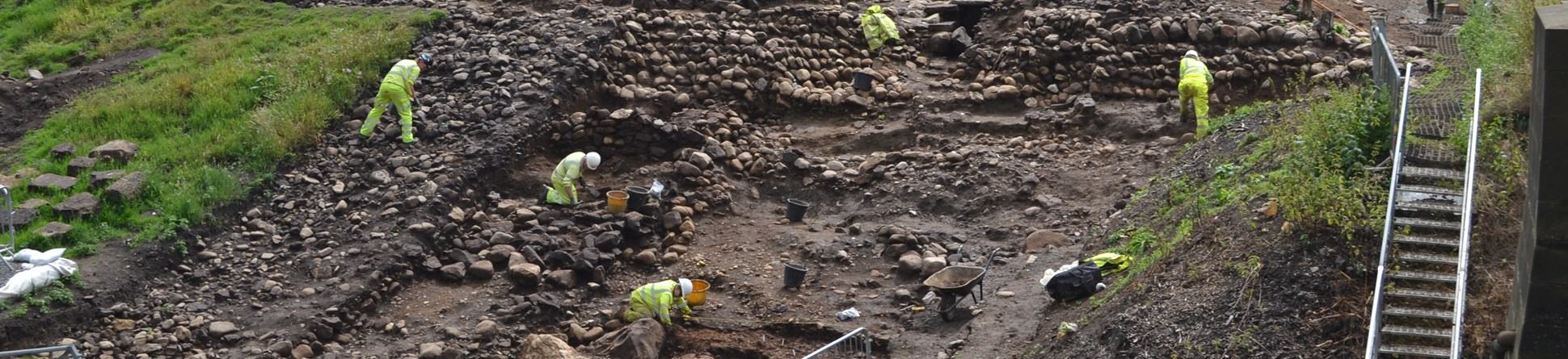Image of archaeologists excavating Roman revetments, built to protect the river shore from erosion. This excavation was carried out in 2014, East of A1 on the south side of the River Swale near Catterick.